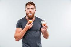 Ακάθαρτος γενειοφόρος νεαρός άνδρας που τρώει τα κέικ κρέμας Στοκ εικόνες με δικαίωμα ελεύθερης χρήσης