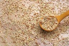 Ακέραιο ρύζι σε ένα ξύλινο κουτάλι και σιτάρια γύρω στοκ εικόνες με δικαίωμα ελεύθερης χρήσης