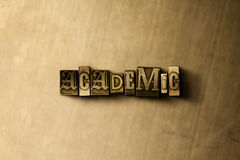 ΑΚΑΔΗΜΑΪΚΟΣ - κινηματογράφηση σε πρώτο πλάνο της βρώμικης στοιχειοθετημένης τρύγος λέξης στο σκηνικό μετάλλων Στοκ εικόνες με δικαίωμα ελεύθερης χρήσης