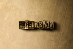 ΑΚΑΔΗΜΙΑ - κινηματογράφηση σε πρώτο πλάνο της βρώμικης στοιχειοθετημένης τρύγος λέξης στο σκηνικό μετάλλων Στοκ φωτογραφία με δικαίωμα ελεύθερης χρήσης