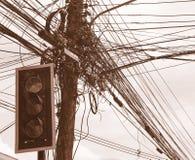 Ακατάστατα ηλεκτρικά καλώδια και καλώδια στον ηλεκτρικό πόλο μπροστά από τους φωτεινούς σηματοδότες Στοκ εικόνες με δικαίωμα ελεύθερης χρήσης