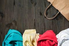 Ακατάστατα διπλωμένα ενδύματα και μια τσάντα εγγράφου Στοκ Εικόνες