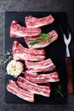 Ακατέργαστα άψητα πλευρά χοιρινού κρέατος, φρέσκο κρέας στο σκοτεινό υπόβαθρο μετάλλων Τοπ όψη στοκ φωτογραφίες