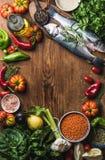 Ακατέργαστα άψητα seabass ψάρια, λαχανικά, σιτάρια, χορτάρια, καρυκεύματα και ελαιόλαδο στον αγροτικό ξύλινο τεμαχίζοντας πίνακα  Στοκ Εικόνα