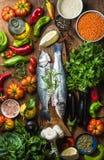 Ακατέργαστα άψητα seabass ψάρια, λαχανικά, σιτάρια, χορτάρια, καρυκεύματα ρυζιού και ελαιόλαδο στον αγροτικό ξύλινο τεμαχίζοντας  Στοκ Φωτογραφία