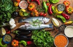 Ακατέργαστα άψητα seabass ψάρια με τα λαχανικά, τα σιτάρια, τα χορτάρια και τα καρυκεύματα στον τεμαχίζοντας πίνακα πέρα από το α Στοκ Εικόνα