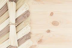 Ακατέργαστα ασιατικά νουντλς στο μαλακό μπεζ ξύλινο πίνακα με το διάστημα αντιγράφων ως διακοσμητικό πλαίσιο συνόρων, τοπ άποψη Στοκ εικόνα με δικαίωμα ελεύθερης χρήσης