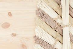 Ακατέργαστα ασιατικά νουντλς στο μαλακό μπεζ ξύλινο πίνακα με το διάστημα αντιγράφων ως διακοσμητικό πλαίσιο συνόρων, τοπ άποψη Στοκ Εικόνες