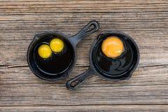 Ακατέργαστα αυγά στο τηγάνι στο παλαιό ξύλινο υπόβαθρο Στοκ εικόνα με δικαίωμα ελεύθερης χρήσης