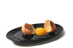 Ακατέργαστα αυγό και κοχύλι αυγών στο μαύρο πιάτο Στοκ Φωτογραφία