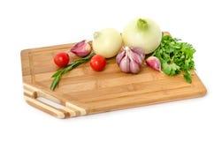 Ακατέργαστα λαχανικά στον τέμνοντα πίνακα στο άσπρο υπόβαθρο Στοκ Εικόνες