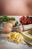 Ακατέργαστα ζυμαρικά αυγών με το αλεύρι και την κυλώντας καρφίτσα Στοκ Εικόνες