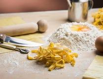 Ακατέργαστα ζυμαρικά αυγών με το αλεύρι και την κυλώντας καρφίτσα Στοκ Φωτογραφίες