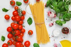 Ακατέργαστα ζυμαρικά με τις ντομάτες, το βασιλικό, τα καρυκεύματα και το ελαιόλαδο πέρα από τον άσπρο μαρμάρινο πίνακα Έννοια μαγ Στοκ φωτογραφία με δικαίωμα ελεύθερης χρήσης