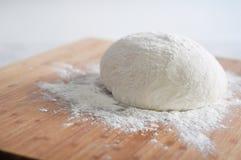 Ακατέργαστα ζύμη και αλεύρι ψωμιού στο ξύλινο πιάτο στοκ εικόνα με δικαίωμα ελεύθερης χρήσης