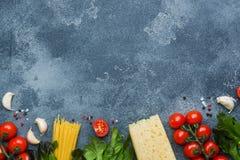 Ακατέργαστα ιταλικά πράσινα τυριών ντοματών κερασιών συστατικών μακαρονιών και μαγειρέματος ζυμαρικών Ιταλικό υπόβαθρο πετρών τρο στοκ φωτογραφίες