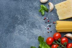 Ακατέργαστα ιταλικά πράσινα τυριών ντοματών κερασιών συστατικών μακαρονιών και μαγειρέματος ζυμαρικών Ιταλικό υπόβαθρο πετρών τρο στοκ φωτογραφία