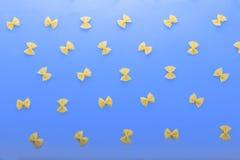 Ακατέργαστα και φρέσκα ζυμαρικά υπό μορφή πεταλούδων σε ένα μπλε υπόβαθρο farfalle ζυμαρικά άψητα Προϊόντα αλευριού Ζυμαρικά Riga στοκ εικόνα με δικαίωμα ελεύθερης χρήσης