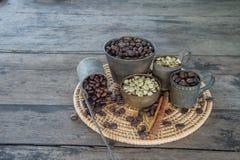 Ακατέργαστα και ψημένα φασόλια καφέ με το φλυτζάνι ορείχαλκου στον ξύλινο πίνακα Στοκ Φωτογραφίες