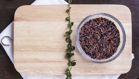 Ακατέργαστα καφετί ρύζι και χορτάρια στο ξύλινο fla υποβάθρου πινάκων τεμαχισμού Στοκ φωτογραφία με δικαίωμα ελεύθερης χρήσης
