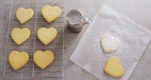 Ακατέργαστα μπισκότα μορφής καρδιών στο δίσκο ψησίματος με το διηθητήρα δονητών αλευριού και το έγγραφο κεριών 4k φιλμ μικρού μήκους