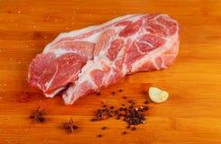 Ακατέργαστα μπριζόλα μπριζολών χοιρινού κρέατος τοπ άποψης και σκόρδο, ξύλινο υπόβαθρο πιπεριών Στοκ Φωτογραφίες