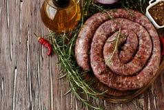 Ακατέργαστα λουκάνικα βόειου κρέατος σε μια παν, εκλεκτική εστίαση χυτοσιδήρων Στοκ φωτογραφία με δικαίωμα ελεύθερης χρήσης
