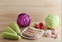 Ακατέργαστα λουκάνικα κρέατος kupaty και λαχανικά Στοκ Εικόνες