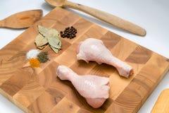 Ακατέργαστα πόδια κοτόπουλου και βασικά καρυκεύματα στο χειροποίητο ξύλινο πίνακα και το Κ στοκ εικόνα με δικαίωμα ελεύθερης χρήσης