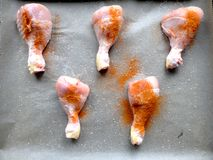 Ακατέργαστα πόδια κοτόπουλου που προετοιμάζονται για το μαγείρεμα στο φούρνο σε παν και υποστηρίζοντας χαρτί ψησίματος με το αλατ στοκ εικόνα