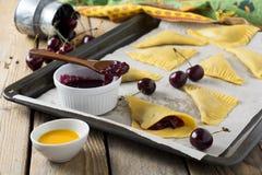 Ακατέργαστα συστατικά για τα σπιτικά κέικ με το κεράσι σε ένα σκοτεινό ξύλινο υπόβαθρο Στοκ φωτογραφία με δικαίωμα ελεύθερης χρήσης