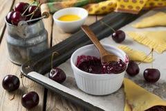 Ακατέργαστα συστατικά για τα σπιτικά κέικ με το κεράσι σε ένα σκοτεινό ξύλινο υπόβαθρο Στοκ εικόνα με δικαίωμα ελεύθερης χρήσης