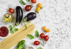 Ακατέργαστα συστατικά για την παραγωγή των ζυμαρικών - μακαρόνια, μελιτζάνα, ντομάτες, πιπέρι, ελαιόλαδο, σάλτσα ντοματών και βασ Στοκ Φωτογραφίες