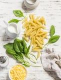Ακατέργαστα συστατικά για την παραγωγή των ζυμαρικών με το σπανάκι να αποβουτυρώσουν τη σάλτσα - penne ζυμαρικά, φρέσκο σπανάκι,  Στοκ φωτογραφίες με δικαίωμα ελεύθερης χρήσης