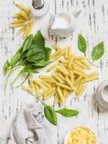Ακατέργαστα συστατικά για την παραγωγή των ζυμαρικών με το σπανάκι να αποβουτυρώσουν τη σάλτσα - penne ζυμαρικά, φρέσκο σπανάκι,  Στοκ εικόνα με δικαίωμα ελεύθερης χρήσης