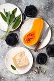 Ακατέργαστα συστατικά για την παραγωγή των μαύρων ζυμαρικών με το butternut να συμπιέσουν, το τυρί παρμεζάνας και τη φασκομηλιά Μ Στοκ φωτογραφίες με δικαίωμα ελεύθερης χρήσης