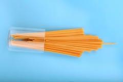 Ακατέργαστα, φρέσκα και οργανικά μακαρόνια σε ένα φωτεινό μπλε υπόβαθρο Κίτρινα ξηρά ζυμαρικά και μακαρόνια για το ιταλικό συστατ Στοκ Φωτογραφία
