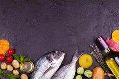 Ακατέργαστα φρέσκα ψάρια dorado με τους νεαρούς βλαστούς των Βρυξελλών, τις ντομάτες, το λεμόνι, τη νέα πατάτα και τα πράσινα Στοκ Εικόνες