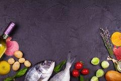 Ακατέργαστα φρέσκα ψάρια dorado με τους νεαρούς βλαστούς των Βρυξελλών, τις ντομάτες, το λεμόνι, τη νέα πατάτα και τα πράσινα Στοκ εικόνα με δικαίωμα ελεύθερης χρήσης