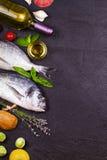 Ακατέργαστα φρέσκα ψάρια dorado με τους νεαρούς βλαστούς των Βρυξελλών, τις ντομάτες, το λεμόνι, τη νέα πατάτα και τα πράσινα Στοκ Φωτογραφίες