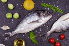 Ακατέργαστα φρέσκα ψάρια dorado με τους νεαρούς βλαστούς των Βρυξελλών, τις ντομάτες, το λεμόνι, τη νέα πατάτα και τα πράσινα Στοκ εικόνες με δικαίωμα ελεύθερης χρήσης