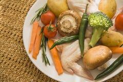 Ακατέργαστα φτερά κοτόπουλου και vegetbles στο υπόβαθρο αχύρου στοκ εικόνες