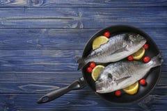 Ακατέργαστα ψάρια με τις ντομάτες λεμονιών και κερασιών στο τηγάνι Στοκ Φωτογραφία