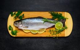 Ακατέργαστα ψάρια πεστροφών που προετοιμάζονται για το μαγείρεμα και στον ξύλινο τσακώνοντας πίνακα Στοκ Εικόνες