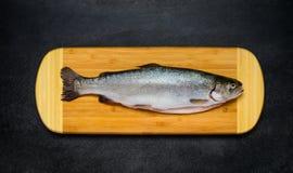 Ακατέργαστα ψάρια πεστροφών στον ξύλινο τεμαχίζοντας πίνακα Στοκ εικόνες με δικαίωμα ελεύθερης χρήσης