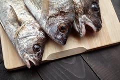 Ακατέργαστα ψάρια στον ξύλινο τέμνοντα πίνακα Στοκ φωτογραφία με δικαίωμα ελεύθερης χρήσης