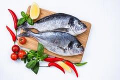 Ακατέργαστα ψάρια dorado στον ξύλινο τέμνοντα πίνακα με τα λαχανικά στον άσπρο πίνακα στοκ φωτογραφίες