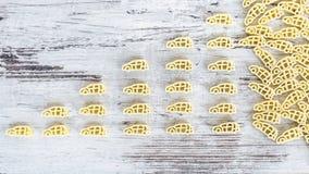 Ακατέργαστα όχημα-διαμορφωμένα ζυμαρικά στο σωρό στον ξύλινο πίνακα Στοκ Εικόνα