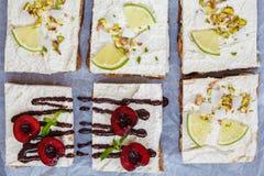 Ακατέργαστα cheesecakes φυστικιών, καρύδων, ασβέστη και σοκολάτα-κερασιών Στοκ Εικόνες