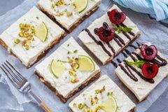 Ακατέργαστα cheesecakes φυστικιών, καρύδων, ασβέστη και σοκολάτα-κερασιών Στοκ εικόνα με δικαίωμα ελεύθερης χρήσης